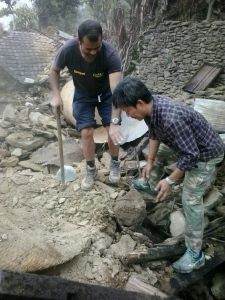 R4C Team Member Deependra helps his relatives dig through the rubble of their home